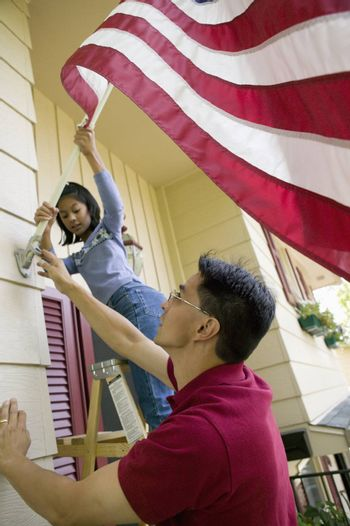 Father and daughter put a US flag on their house