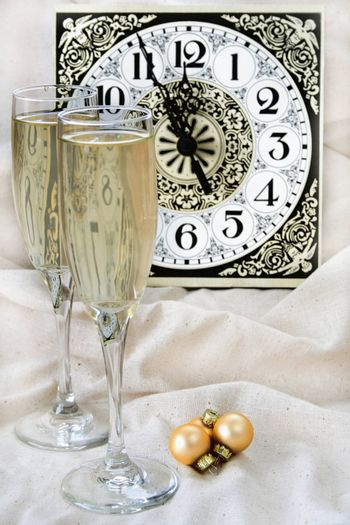 Wine glasses and ornaments with a clock in the background showing that it is almost midnight.