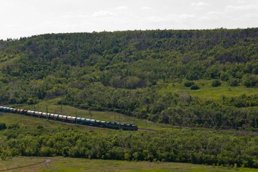Freight Train Going by Railway Against Summer Landscape