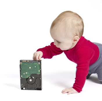 young child in white background with hard drive. red shirt and blue trousers
