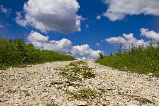 Countryside stone road in fields and blue sky with clouds
