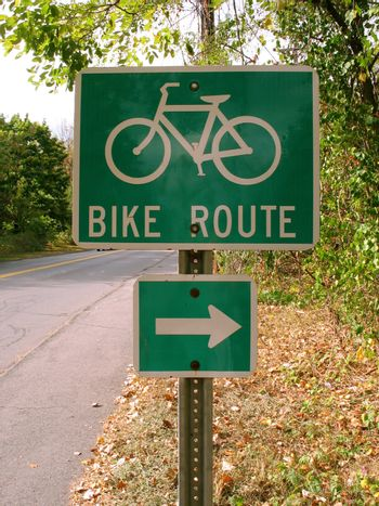 A green bike route sign on the side of the path.