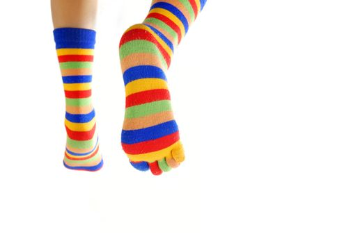Close-up photo of the legs in colored socks going away