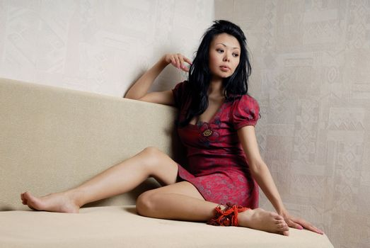 Graceful Asian woman sitting in white sofa