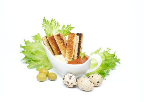 Snack from crackling bread with cheese sauce and a BBQ ketchup, leaves of salad and olives