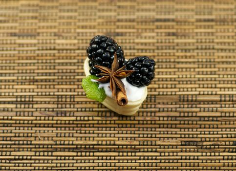 Small baskets from shortcake dough with whipped cream, a blackberry, cinnamon and anise