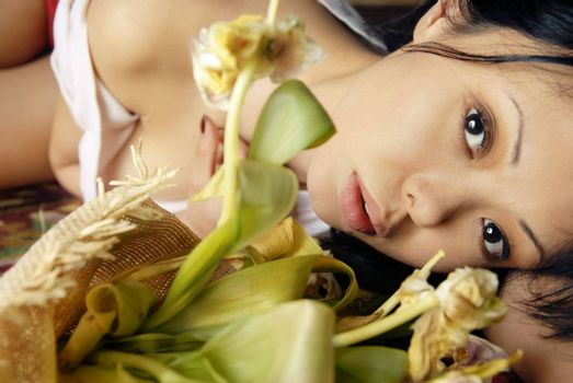 Sensual portrait of sorrowful lady laying with flowers