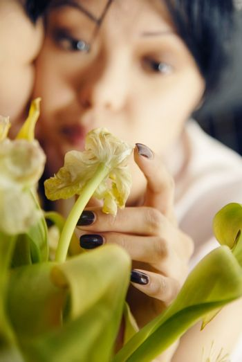 Photo of sad woman touching the plant and waiting for somebody