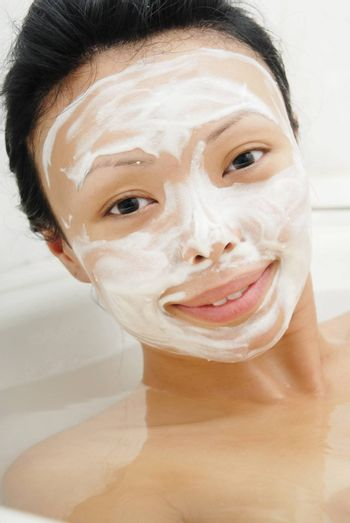 Closeup portrait of the woman in the bath with beauty mask