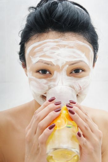 Drinking smiling woman with beauty mask