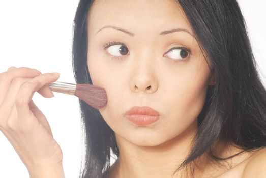 Close-up portrait of the young woman with makeup brush