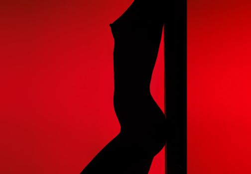 Dancing silhouette of naked woman in back-light on a red background
