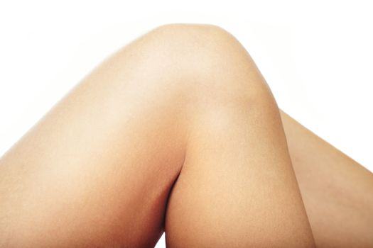 Close-up photo of the woman hips and knee on a white background