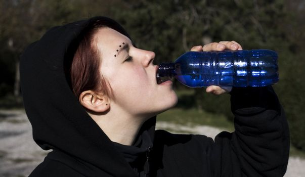 Thirsty girl drinking water on a sunny day.