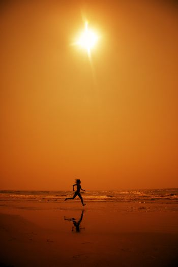 Woman running at the hot beach in the dark night. Artistic red and yellow color toning added