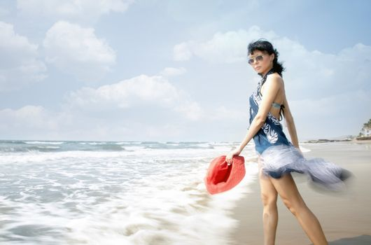 Lady with sunglasses and red hat going into the see. Motion blur added by the long shutter speed for dynamic effect