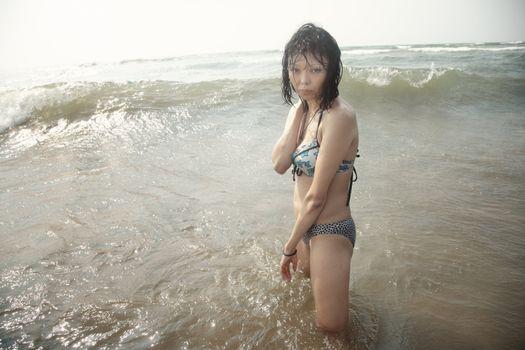 Wet brunette lady in bikini standing in the water