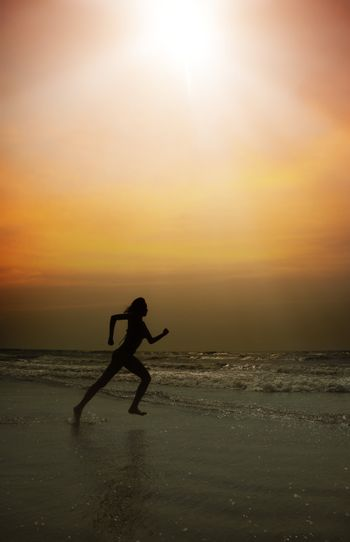 Active lady running at the beach during sunset. Special darkness and colors added