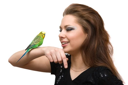 The girl talks to a green parrot