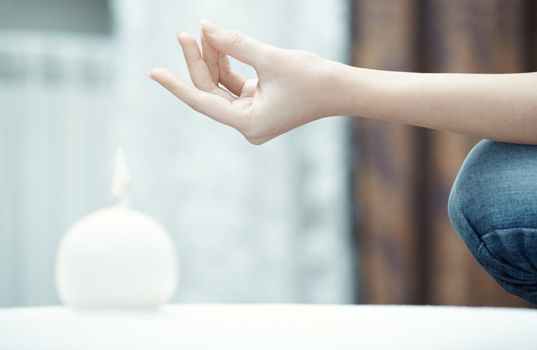 Hand of human practicing yoga at home