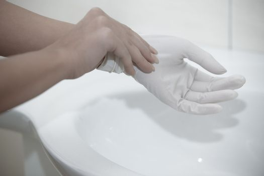Hands of human taking on rubber gloves