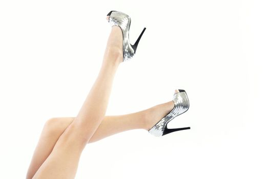 Woman legs in fashionable shoes on a white background