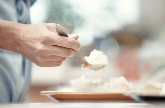 Woman hand holding spoon with rice-milk