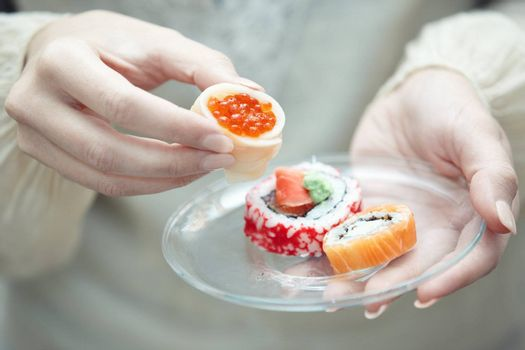 Human hands holding place with sushi
