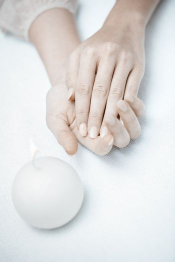 Woman hands in spa saloon with white candle