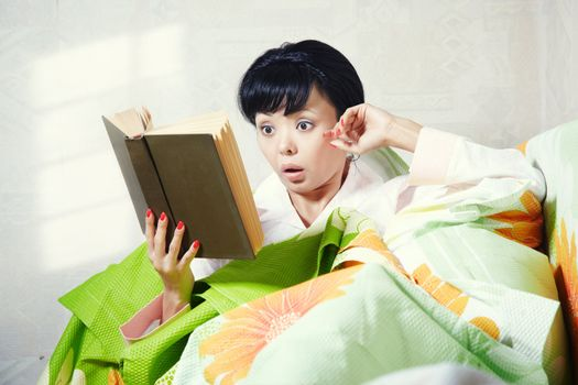 Brunette indoors laying on the bed and reading interesting book