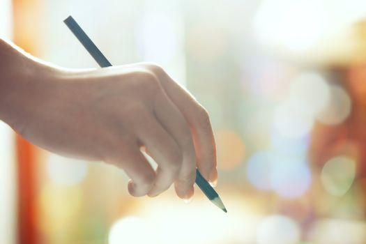 Hand of human holding green pencil