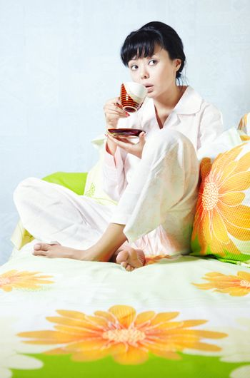 Lady sitting on the bed and drinking coffee
