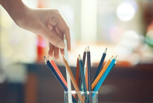 Human hand taking taking pencils