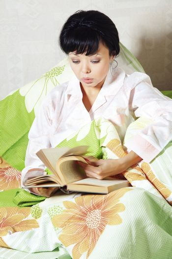 Young brunette indoors reading book on the bed