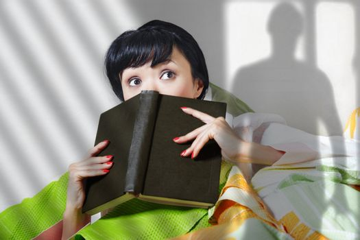 Afraid lady with book indoors looking to somebody. Shade of somebody is on the wall