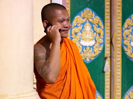 Asian buddhist monk talking with mobile phone in temple