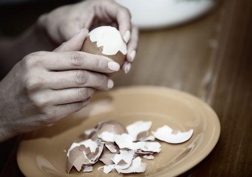 Human hand preparing boiled egg