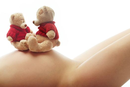 Body of the laying pregnant woman and toys on her belly