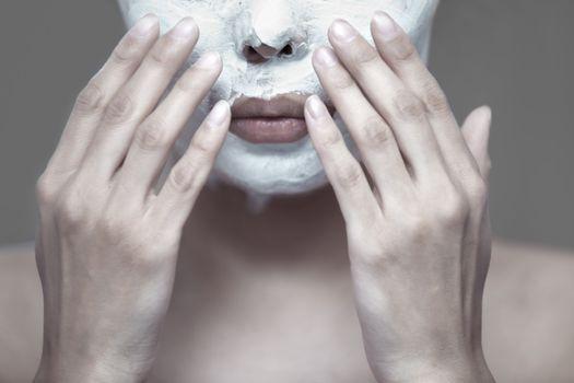 Woman applying moisturizing cream to the face