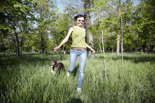 Smiling happy lady runs with her dog in outdoors park