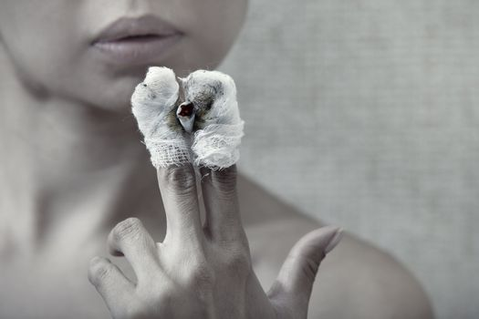Woman with burnt fingers smoking cigarette stub