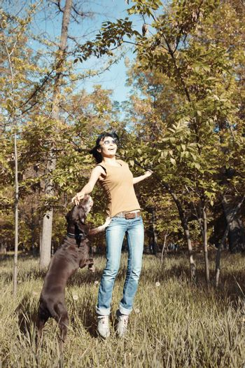 Happy woman playing with dog outdoors