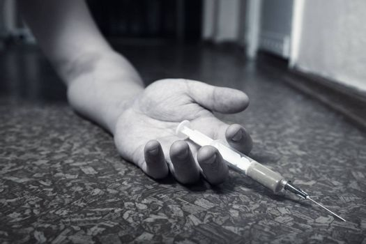 Hand of the narcotist with syringe on the floor. Monochrome photo