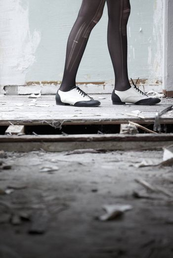 Human legs in stylish shoes standing in the ruined dirty room