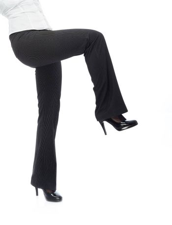Close-up photo of businesswoman legs in black trousers going on a white background