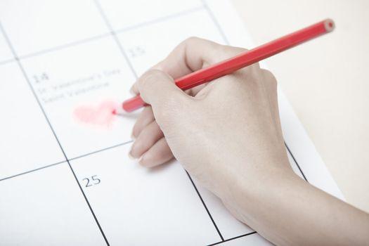 Woman hand drawing heart shape on a calendar