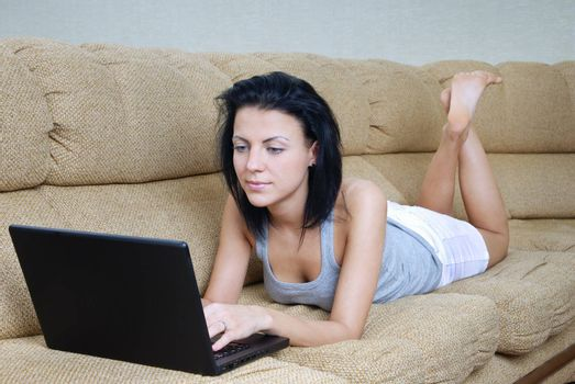 Serene lady laying on sofa and working a laptop
