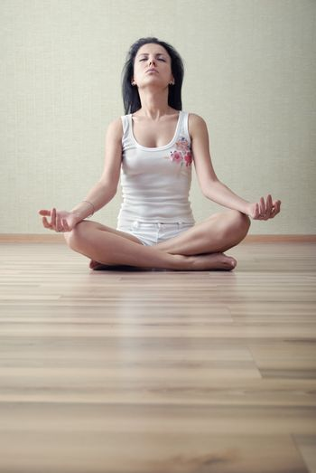 Woman in lotus position meditating in a yoga training