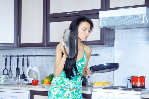 Elegant housewife in the kitchen holding the frying pan