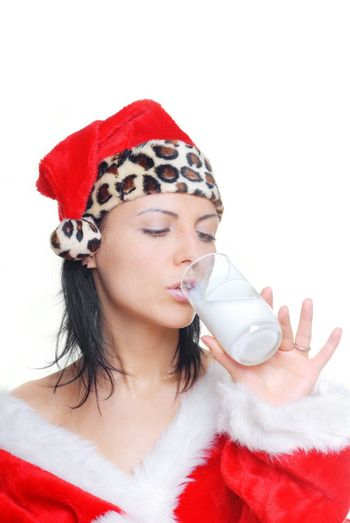 Woman in Santa Claus costume drinking a fresh milk cocktail